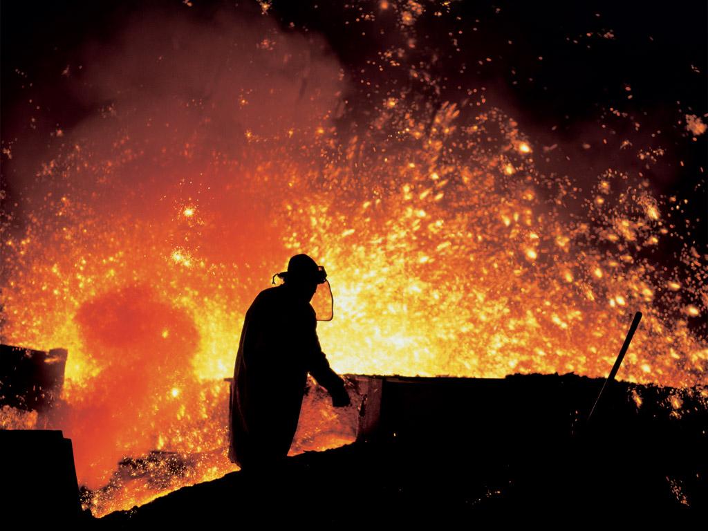 Un métallurgiste travaillant près d'un haut fourneau.