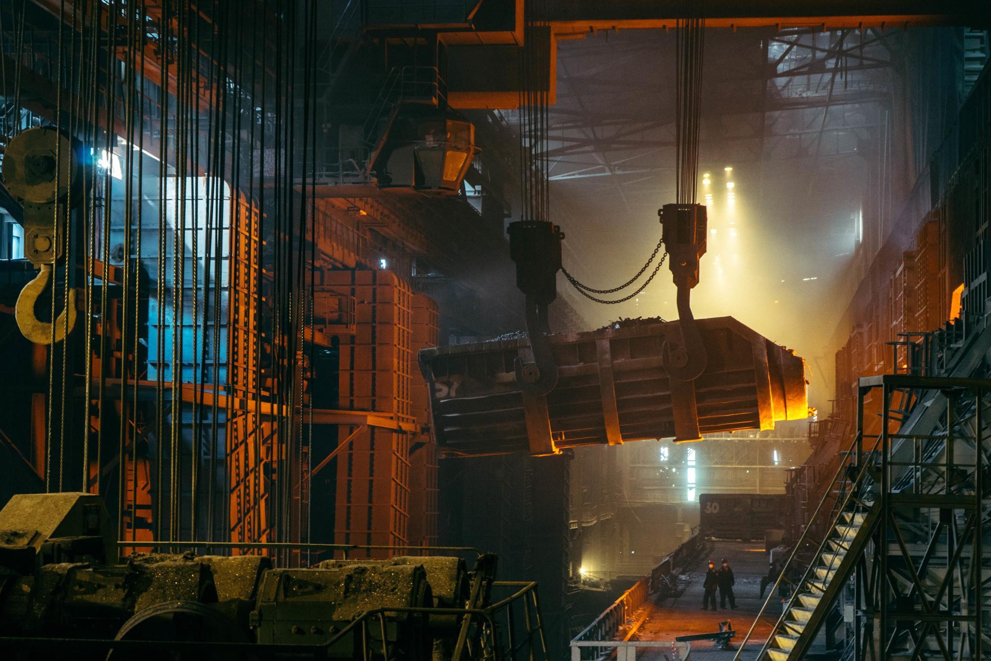 Deux hommes travaillant dans une imposante aciérie.